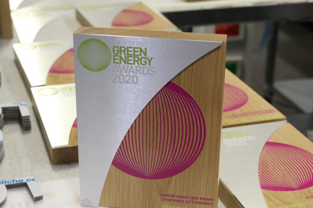 A wooden tablet award with the scottish green energy awards logo. The Award is stood on a manufacturing bench, and the front face has an additional piece of cut aluminium on the left side of the award.