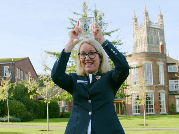 Representative of the Kings School Gloucester stood outside the school holding a custom SoGlos Award trophy in the air