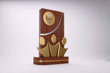 Photo of a bespoke award on a white backdrop. The award has a layered base and a rectangular wooden top, with a sloped cut in the middle. The gold Kings school logo is inset in the top left, and three abstract gold human figures sit on the base of the award.
