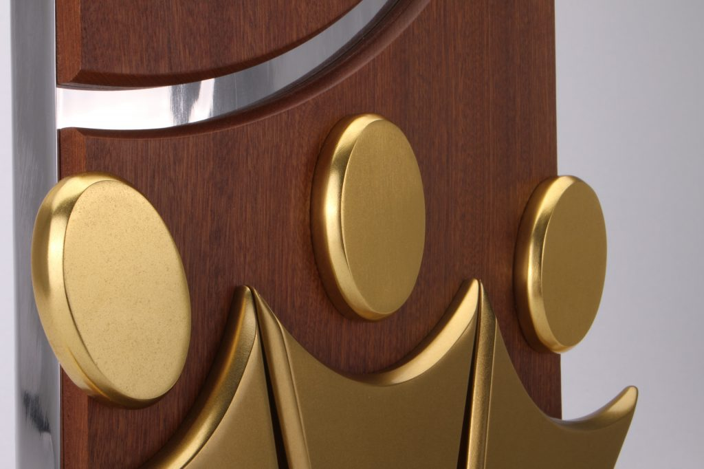 Close-up Photo of a bespoke award on a white backdrop. Three gold abstract human figures made from aluminium sit on a wooden background
