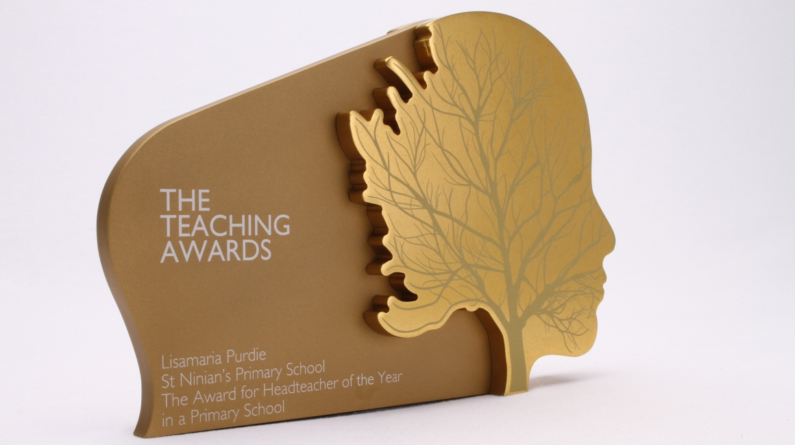 Custom trophy for the teaching awards. The award is a freestanding gold face on a white background
