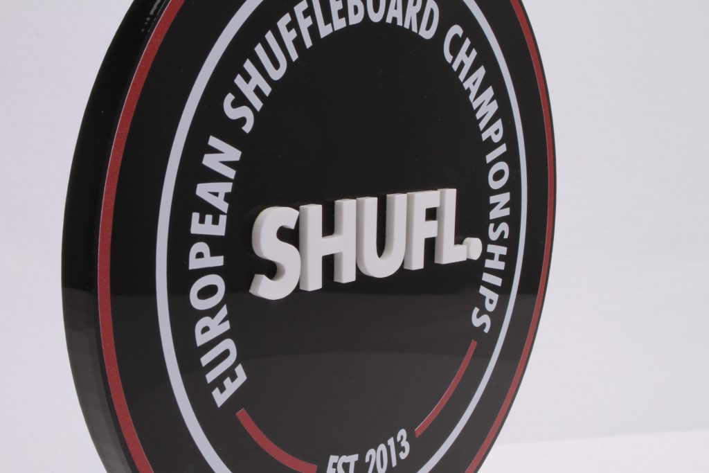 Close up photograph of the custom european shuffleboard award, focused on white acrylic letters on a black background
