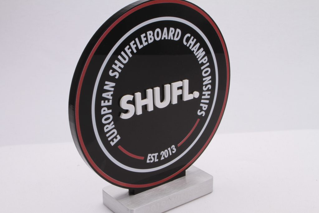 angled photography of European shuffleboard award, a custom trophy with a black top and white letters on an aluminium base